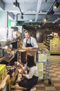 Entrepreneurs arranging packets on shelves in supermarket - MASF12773