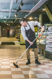 Full length of salesman sweeping floor in grocery store - MASF12779