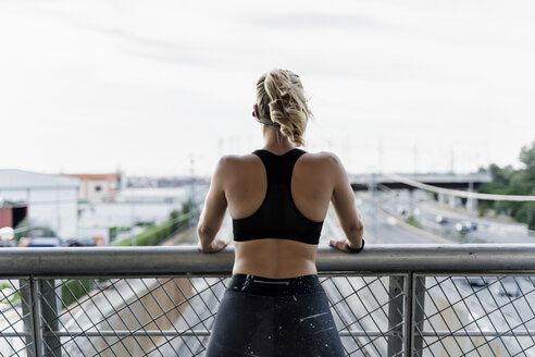 Sporty woman standing on bridge, looking at view - ERRF01471