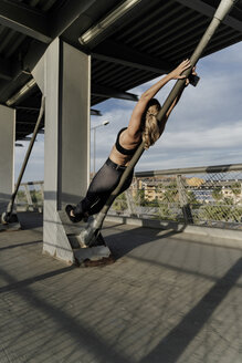 Sporty woman working out o a bridge, leaning on bar - ERRF01477