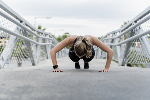 Sporty woman doing push ups, working out on a bridge - ERRF01486