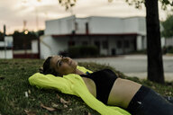 Sporty woman relaxing on grass after workout - ERRF01510