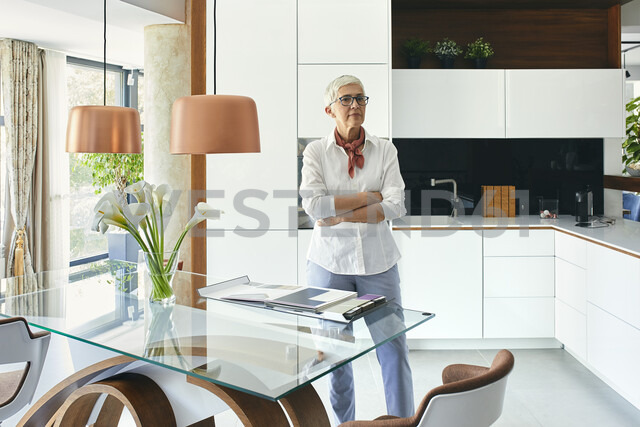 Senior woman sitting on table in showroom of a furniture store, looking at catalogue - ZEDF02296