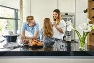 Happy family eating fresh strawberries in modern kitchen - ZEDF02326