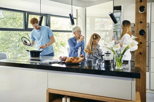 Three genaration family preparing food in kitchen - ZEDF02335