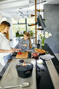 Mother and daughter chopping strawberries in modern kitchen - ZEDF02341