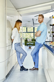Young couple standing in kitchen, talking - ZEDF02344