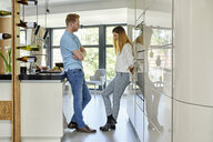 Young couple standing in kitchen, talking - ZEDF02347