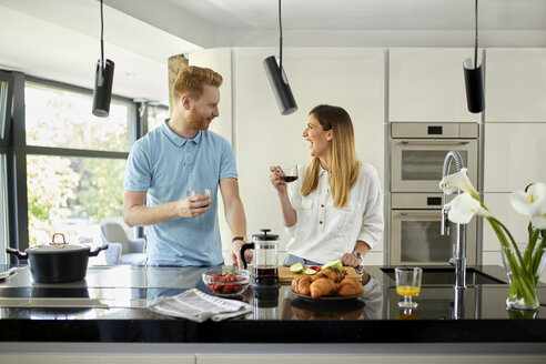 Couple standing in kitchen, preparing healthy breakfast, chopping fruits - ZEDF02350