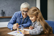 Grandmother and granddaughter sitting at table, painting colouring book - ZEDF02353