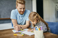 Father and daughter sitting at table, painting colouring book - ZEDF02359