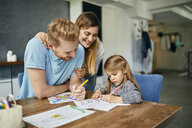 Mother and father watching daughter, painting coloring book - ZEDF02362