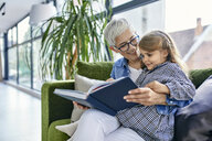 Grandmother sitting on couch with granddaughter, reading book together - ZEDF02368