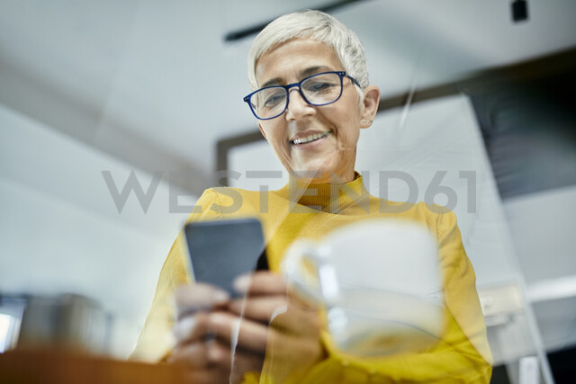 Senior woman drinking coffee, checking text messages on her smartphone - ZEDF02404
