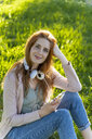 Young redheaded woman with headphones and smartphone in a park - AFVF03180