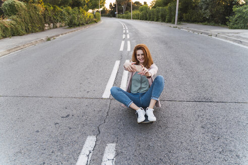 Young woman on skateboard and taking a selfie - AFVF03222