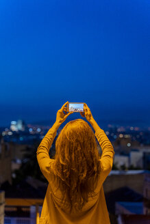 Young woman using smartphone on a view point at blue hour, Barcelona, Spain - AFVF03243