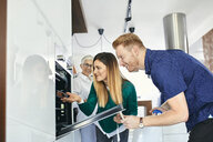 Couple shopping for a new kitchen in showroom - ZEDF02420