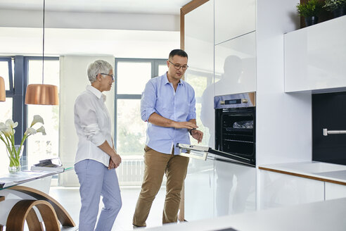 Man and mature woman talking in a kitchen retail store - ZEDF02432