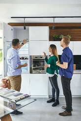 Couple shopping for a new kitchen in showroom - ZEDF02438
