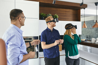 Couple wearing VR glasses shopping for a new kitchen in showroom - ZEDF02441