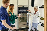 Shop assistant explaining oven to couple shopping for a new kitchen in showroom - ZEDF02447