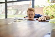 Man examining acrylic resin table in a furniture showroom - ZEDF02468