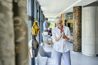 Mature woman in a furniture showroom - ZEDF02474