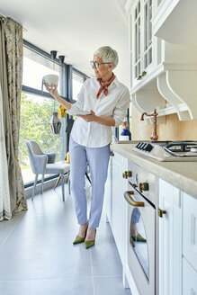 Mature woman looking at bowl in a kitchen furniture showroom - ZEDF02477