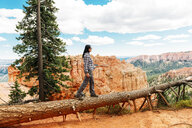 Traveler woman walking on the trunk of a fallen tree enjoying the view in Bryce Canyon, Utah, USA - GEMF02978