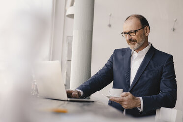 Mature businessman using laptop in a cafe - KNSF05898