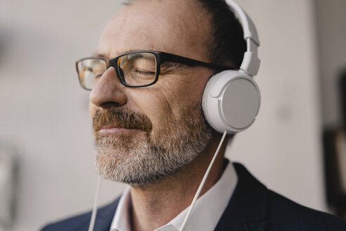 Mature businessman with closed eyes listening to music with headphones - KNSF05901