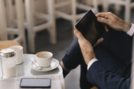 Close-up of businessman using tablet in a cafe - KNSF05913