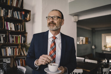 Mature businessman in a cafe with cup of coffee - KNSF05934