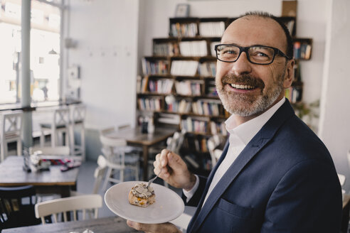 Smiling mature businessman having a piece of cake in a cafe - KNSF05946