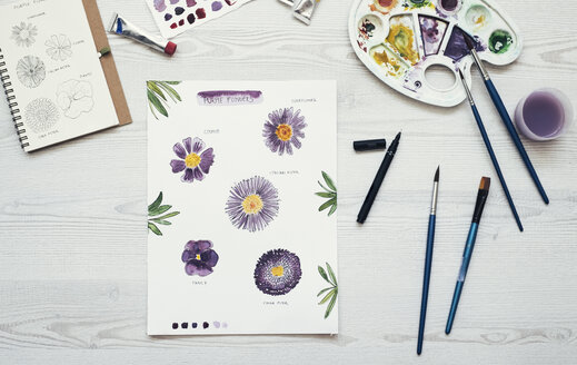 Watercolor painting of purple flowers on the desk, top view - MOMF00704