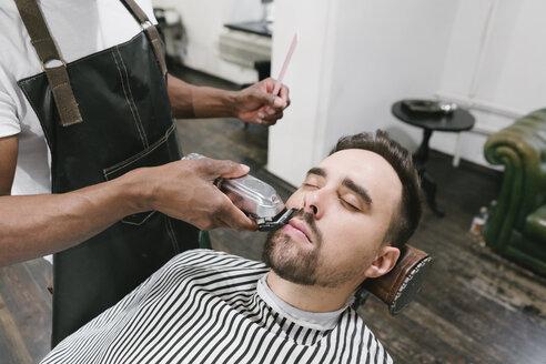 Barber cutting beard of a customer in barber shop - AHSF00495
