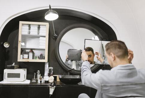 Customer checking his haircut in mirror at barber shop - AHSF00522