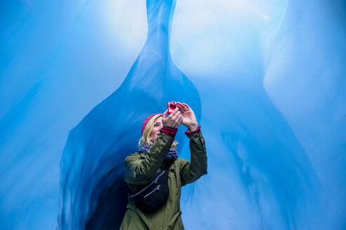 Woman taking a picture in an ice cave, Fox Glacier, South Island, New Zealand - RUNF02482