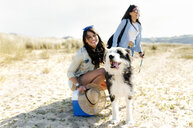 Two happy women with dog on the beach - MGOF04053