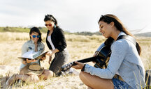 Young woman with friends playing guitar on the beach - MGOF04056