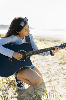 Young woman playing guitar on the beach - MGOF04065