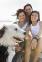Happy female friends with dog on the beach - MGOF04071