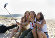 Happy female friends with beer bottles taking a selfie on the beach - MGOF04074