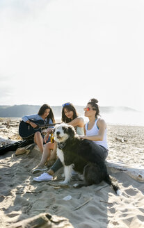 Three women with dog and guitar on the beach - MGOF04083