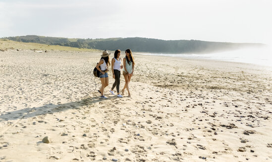 Three women with guitar walking on the beach - MGOF04101