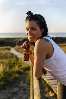 Portrait of a smiling woman with beer bottle in dunes - MGOF04119
