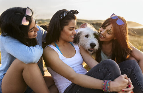 Three happy women with dog sitting in dunes at sunset - MGOF04125