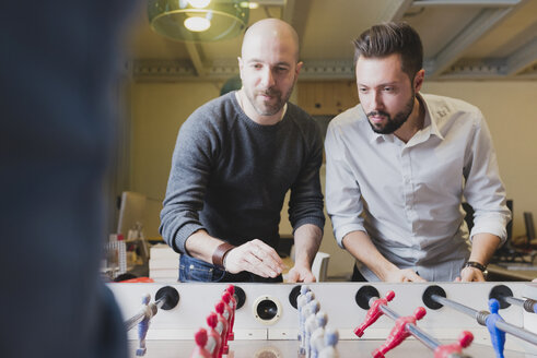 Colleagues playing foosball in office - FMOF00683