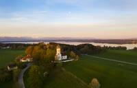 Aerial view over Church St. Johann Baptist and Lake Starnberg at dawn, Holzhausen near Munsing, Bavaria, Germany - LHF00645